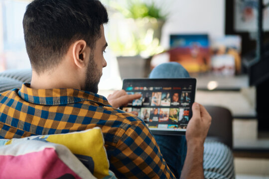 Man Choosing Movie For Streaming On Tablet Computer