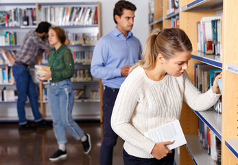 Young happy cheerful positive attractive female student choosing necessary books on shelves in...