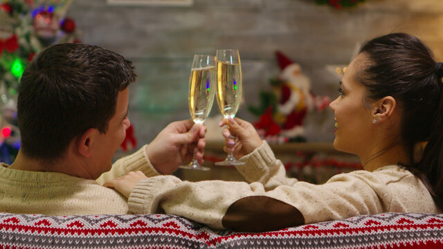 Back view of romantic couple sitting on couch on christmas day with xmas tree in the background. Xmas spirit for caucasian wife and husband celebrating positive happy new year eve sitting whispering