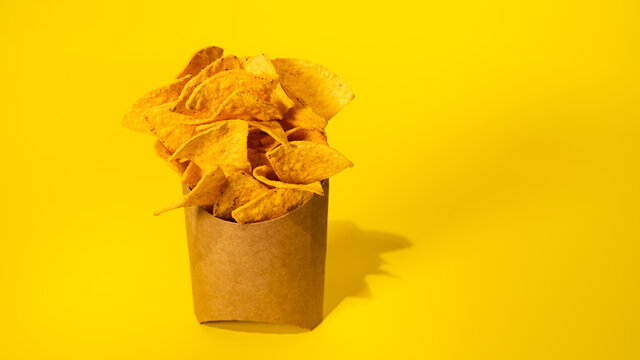 A lot of potato chips  in a paper pack on yellow background