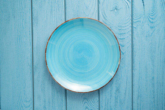TOP VIEW: Empty blue bowl on blue wooden table