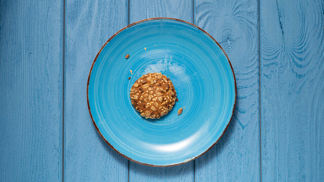TOP VIEW: Last oatmeal cookie on a blue plate on a blue table