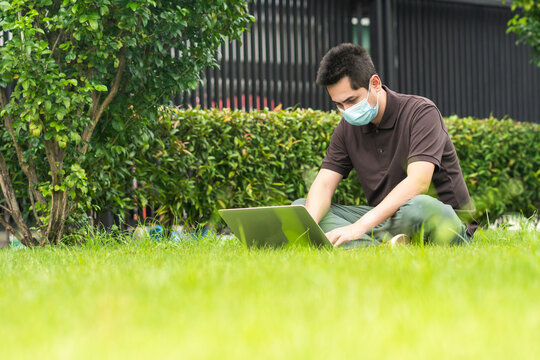 Asian young man using his laptop on a lawn outdoors wearing medical mask to protect others from virus spread