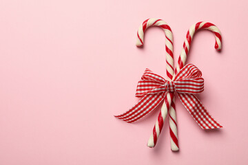 Checkered gift bow with candy canes on pink background