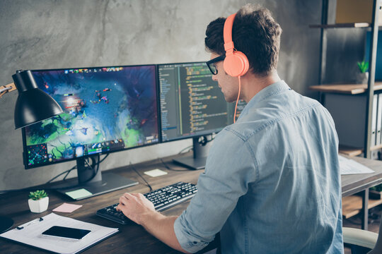 Rear back behind view of his he nice attractive busy focused guy geek playing web network game spending time at modern industrial interior loft concrete wall style work place station
