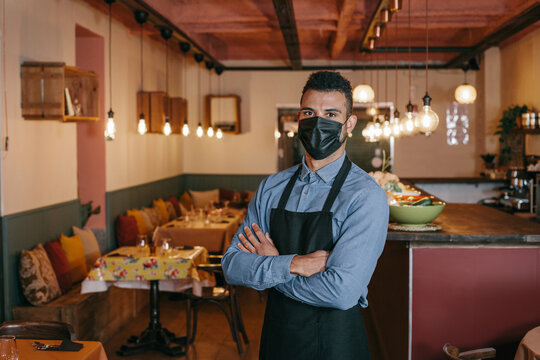 African American businessman wearing a protective black face mask and standing at his restaurant during Coronavirus. Proud owner with his arms crossed and looking at the camera with a defiant gaze.