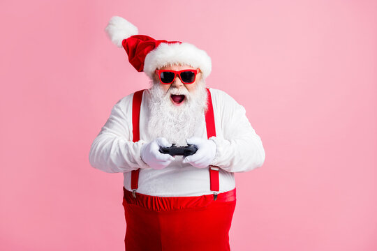Portrait of his he nice cheerful cheery glad focused bearded fat guy Santa father playing console station contest network battle competition air blow wind contest isolated pink pastel color background