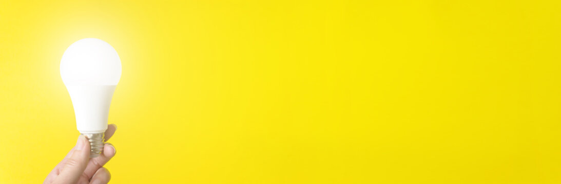 Hand Holding Illuminated Light Bulb Against Yellow Background. Banner format.