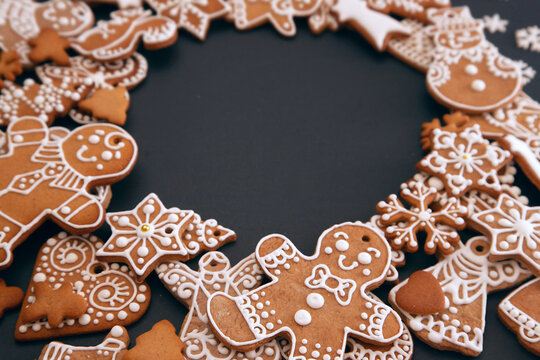 Christmas wreath made from gingerbread cookies with icing and confectionery mastic snowflakes on black background with space for text. Holiday food, homemade baking, Christmas and New Year traditions.