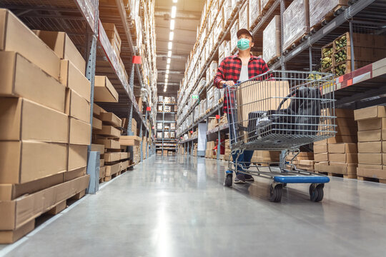 Asian man wearing a shopping mask in Rows of shelves with goods boxes in modern industry warehouse store at factory warehouse storage to decorate the house