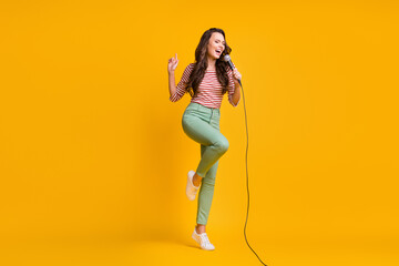 Photo sur Plexiglas Dinosaurs Full length body size photo of girl singing song with microphone in karaoke isolated on bright yellow color background