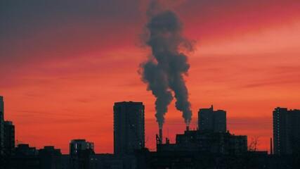 Fotobehang - Smokestacks emitting smoke in red sunset sky over dark city skyline silhouette. Timelapse, 4K UHD.