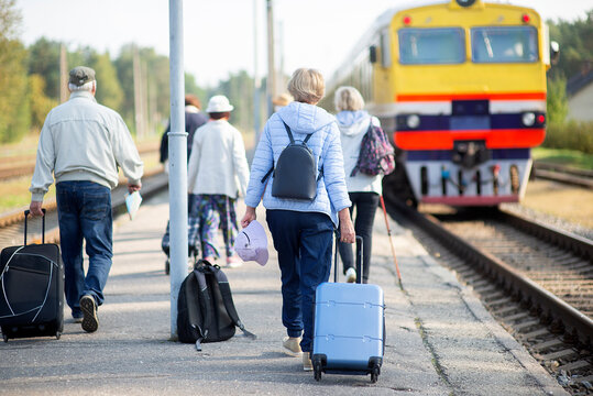 rear view of a group of seniors elderly people waiting for a train to travel
