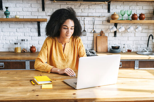 Beautiful multi-ethnic woman using laptop for work at home office . A girl with an afro hairstyle is typing on keyboard answering email. Remote work concept