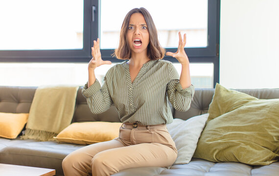 young latin woman screaming with hands up in the air, feeling furious, frustrated, stressed and upset. home concept