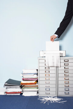 Cropped businessman shredding document besides stack of folders in office