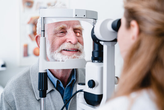 Smiling cheerful elderly patient being checked on eye by female ophthalmic doctor