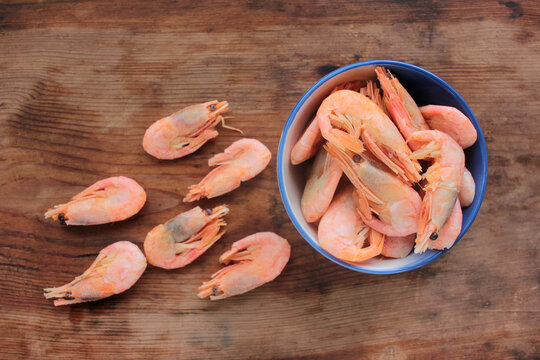 Cooked pink shrimps in the dish. Shell-on North Atlantic prawns in the bowl on rustic wooden table. Top view, copy space