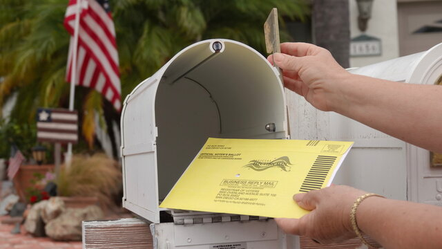 American mailbox with flags, older woman's hands returning mail-in election ballot. Illustrative editorial taken in Vista, CA / USA on October 8, 2020.