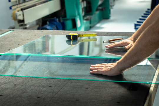 Glazier cuts and breaks glass on a professional table in the workplace