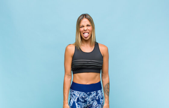 young pretty woman feeling disgusted and irritated, sticking tongue out, disliking something nasty and yucky. fitness concept