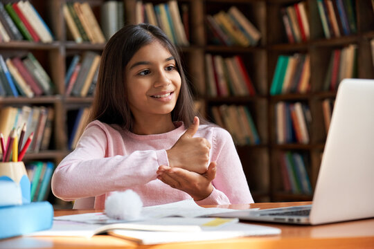 Smiling indian latin deaf disabled child school girl learning online class on laptop communicating with teacher by video conference call using sign language showing hand gesture during virtual lesson.