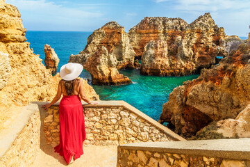 Wall Mural - Landscape with unknown tourist girl is looking to the amazing view of Ponta da Piedade promontory, spectacular rock formations, with caves, grottoes and sea arches in Lagos, Algarve, Portugal