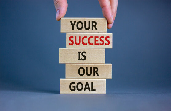 Wooden blocks with text 'your success is our goal'. Male hand. Beautiful grey background, copy space. Business concept.