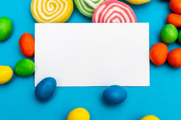 Blank card with multi colored candies on blue. Space for text.