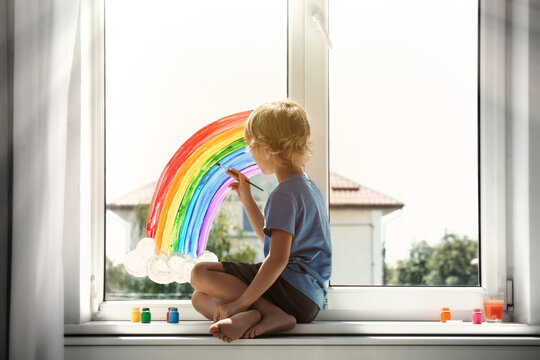 Little boy drawing rainbow on window indoors. Stay at home concept