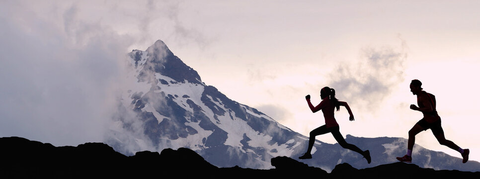 Panoramic banner of running people athletes sport fitness concept. Silhouette trail running in mountain summit background. Man and woman on run training outdoors active fit lifestyle.
