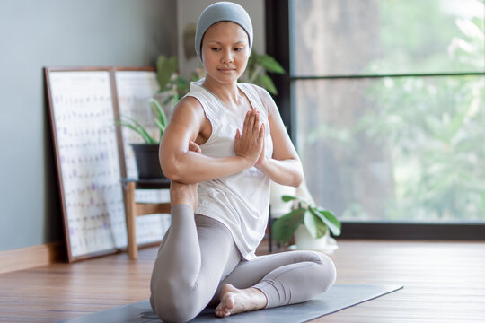 Cancer woman doing yoga at home