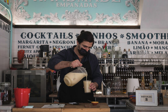 A middle age waiter working alone in a small food shop in Lisbon, Portugal. Restaurant owner of a small enterprise pouring fresh juice from a jar into a glass. Small business entrepreneur struggling