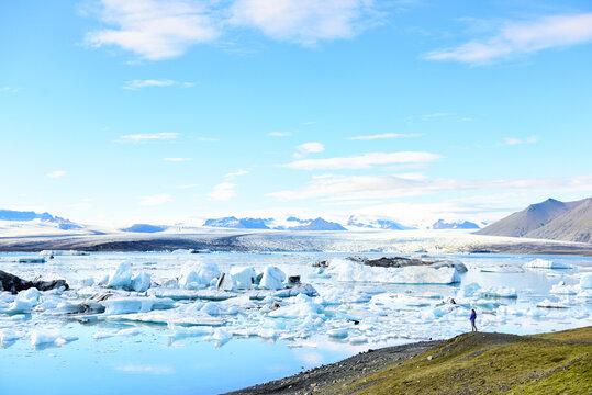 Iceland travel tourist enjoying view of nature landscape Jokulsarlon glacial lagoon / glacer lake on Iceland. Woman outdoors by tourist destination landmark attraction. Vatnajokull National Park.