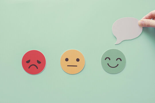 Hand holding speech bubble on happy smile face paper cut, good feedback rating and positive customer review, experience, satisfaction survey ,mental health assessment concept