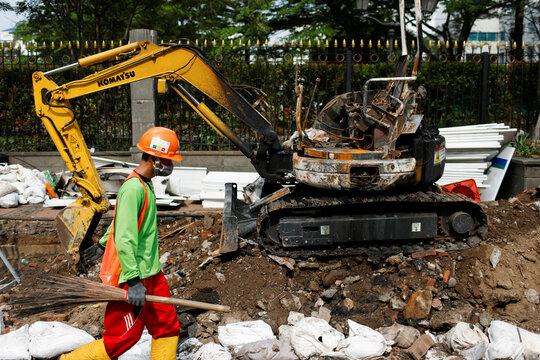 A worker carries a broom past a burned excavator at the second phase MRT project construction site a day after a protest against the government's controversial jobs creation law, in Jakarta