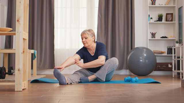 Old woman stretching legs sitting on yoga mat in living room. Active healthy lifestyle sporty old person training workout home wellness and indoor exercising