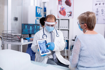Photo sur Plexiglas Dinosaurs Doctor in hospital room explaining x-ray on tablet for senior woman during consultation in clinic room. Medical examination for infections, disease and diagnosis.