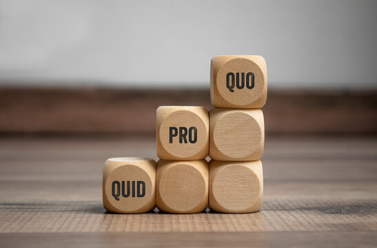 Cubes and dice with business message quid pro quo on wooden background