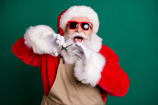 Close-up portrait of his he nice attractive glad cheerful cheery Santa father cutting beard modern hairstyle having fun wearing apron fluffy gloves isolated over green color background