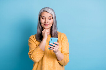 Photo of minded old woman use smartphone think thoughts decide texting typing social media chatting wear style stylish jumper isolated over blue color background Wall mural