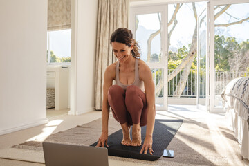 Woman watching online exercise class and working out at home Wall mural