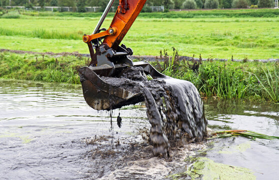 Dredging: crane with backhoe takes a scoop of sediment from a canal
