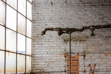 Brick wall painted in white with frosted windows and random pipe in an abandoned factory