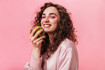 Nice girl in good mood holding green apple on pink background