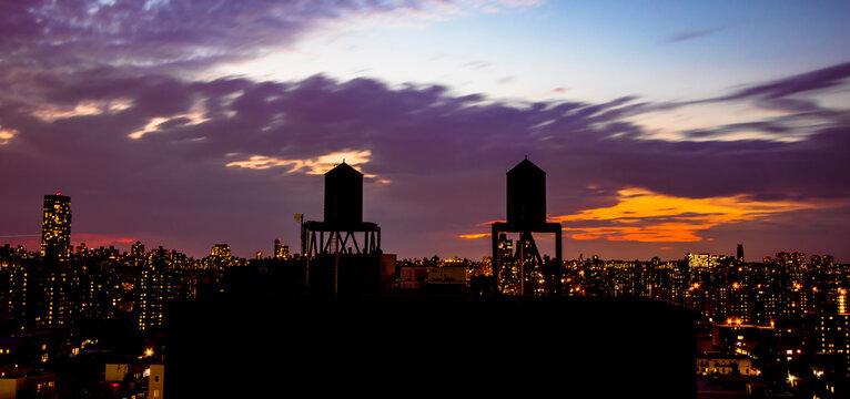 Die Silhouette von zwei Wassertanks über den Dächern Harlems am späten Abend. Der Himmel ist wolkig und in sattem blau und orange gefärbt. Im Hintergrund die Skyline von New York City