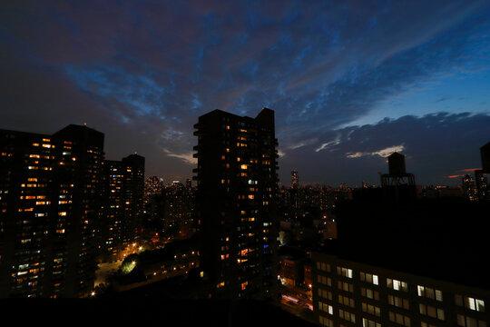 Blick auf einen Wolkenkratzer von Harlems bei Nacht, große Silhouetten und ein bewölkter Himmel. Das Stadtlicht leuchtet im Dunst.