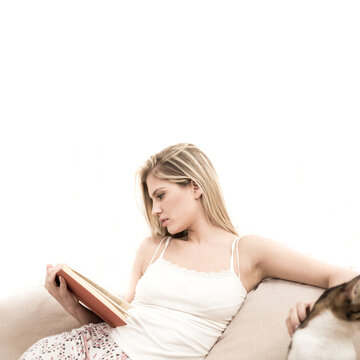 A young blonde sits on a sofa and reads a book. As she reads the book, she caresses her cat. She is very serious.