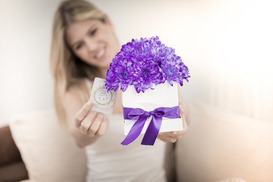 The young blonde holds a bouquet of flowers in her hands in a decorative box she received from a man she loves. She laughs and is very happy.