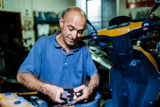 Old mechanic working in his workshop of motorcycles and mopeds. Ambient light,